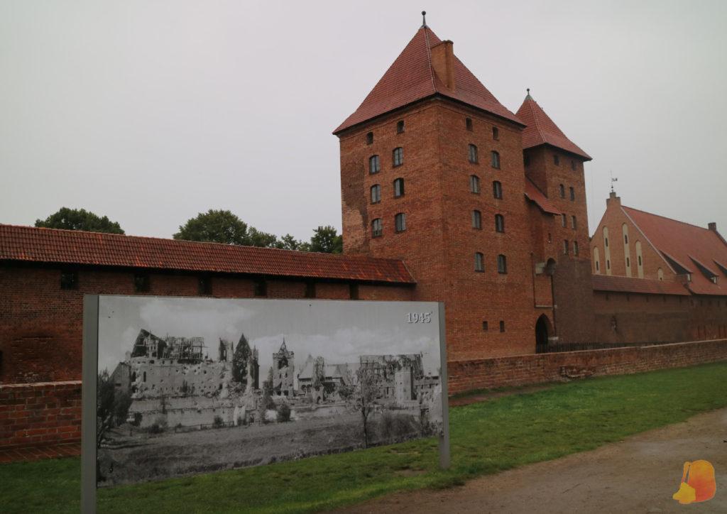 En la foto se ve un cartel de como había quedado el castillo tras la Segunda Guerra Mundial (derruido) y detrás se ve el resultado de la restauración