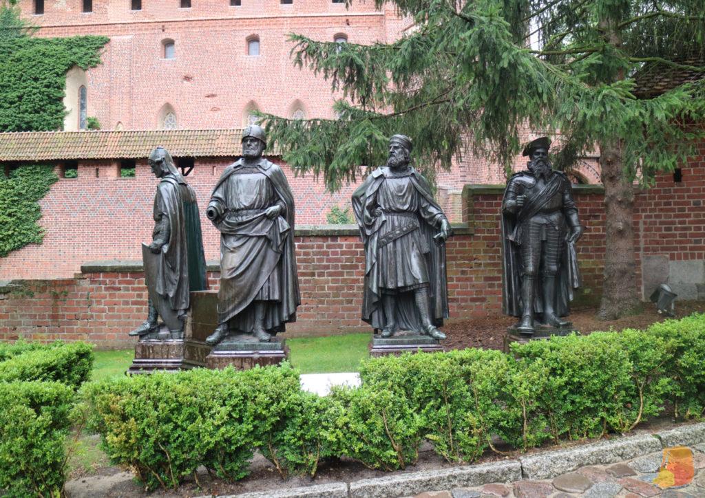 Cuatro estatuas de metal de de maestres y personajes ilustres.