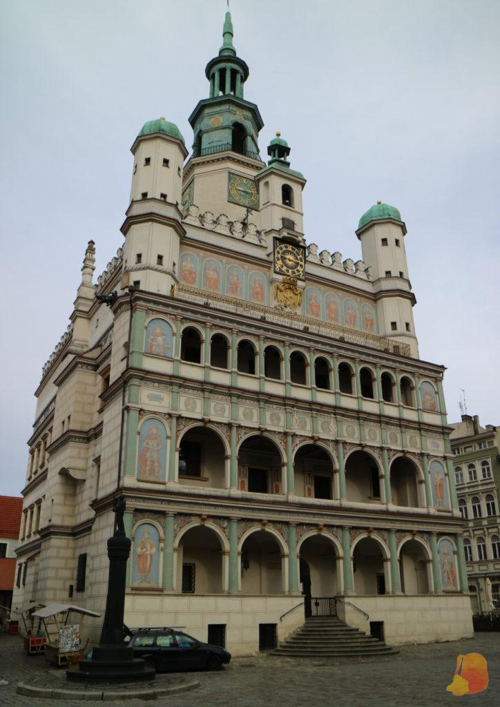La fachada del ayuntamiento está pintada y tiene tres filas de arcos. Delante se ve la picota