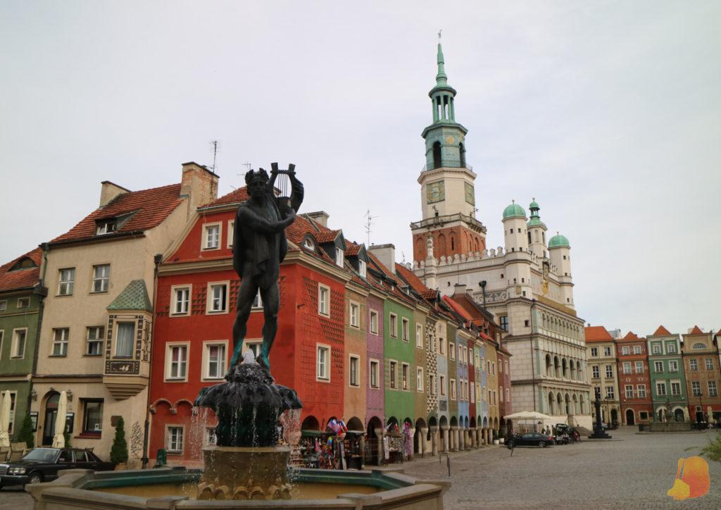 En primer plano tenemos la estatua de Apolo con una lira, detrás las casas de colores y más atrás el ayuntamiento