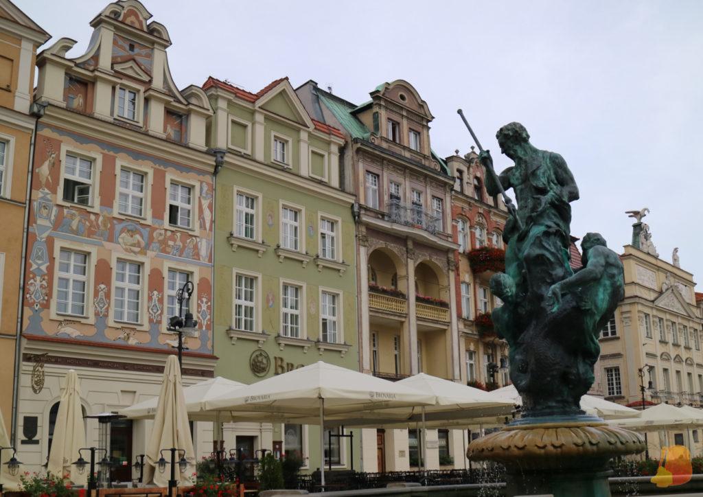 Estatua de Neptuno con su tridente frente a las fachadas de colores que rodean la plaza