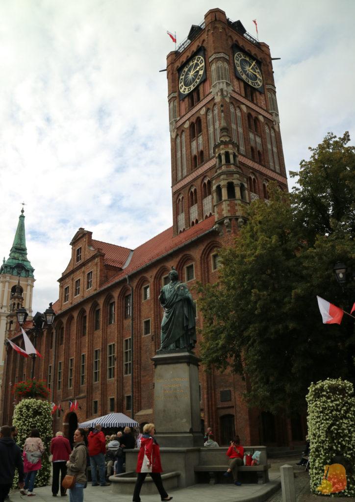 Frente a la gran torre del reloj de ladrillo rojo está la estatua más famosa de Copernico