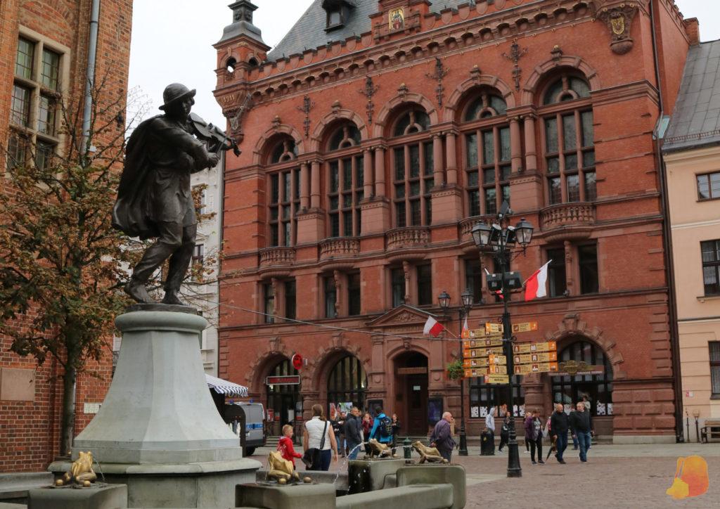 El primer plano está la estatua del barquero tocando el violin y en segundo plano la Casa de Artus de ladrillo rojo y con unos ventanales preciosos