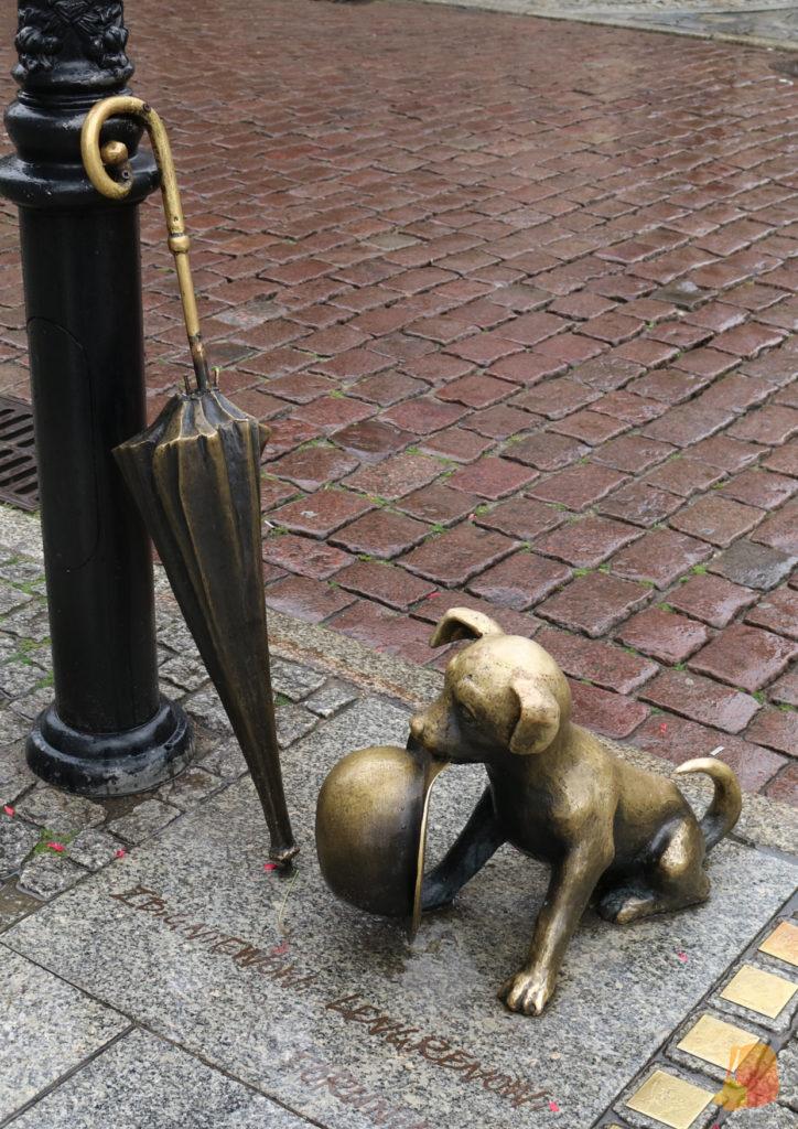 Estatua de un perro sujetando un sombrero con la boca y sentado junto a un paraguas que reposa apoyado en la farola