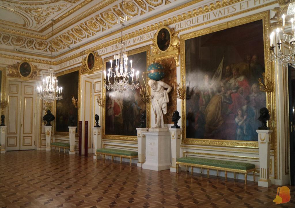 Sala del castillo decorada de blanco y dorado y con cuadros. En el centro hay una estatua de un atlante cargando un cuerpo celeste sobre los hombros