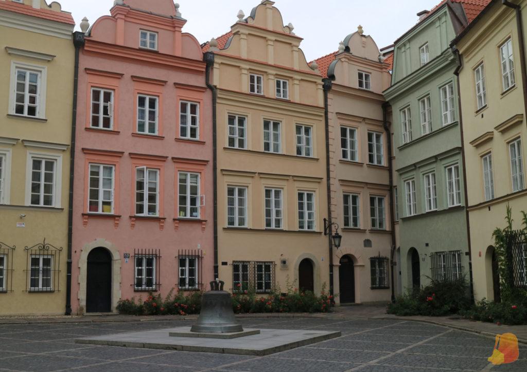 Entre fachadas de colores se encuentra una campana en el medio de la plaza