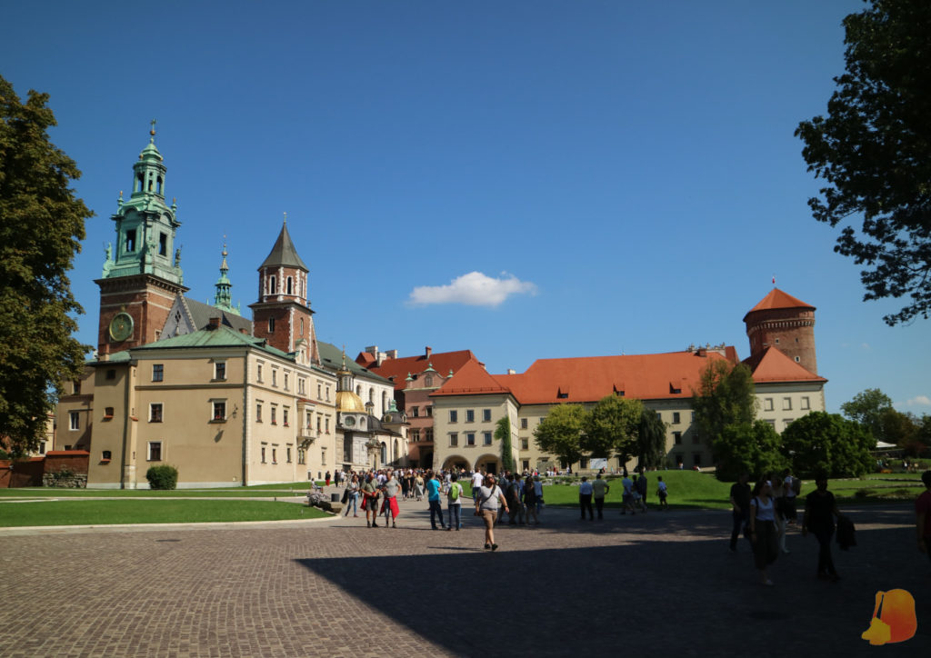 Hay una gran explanada con césped y un paseo. De fondo se ve la Catedral y el Palacio Real