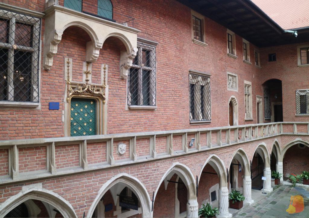 Claustro del Collegius Maius a dos alturas. De la parte baja destacan las arcadas y en la pasarela superior se ven puertas y ventanas de dicentes estilos