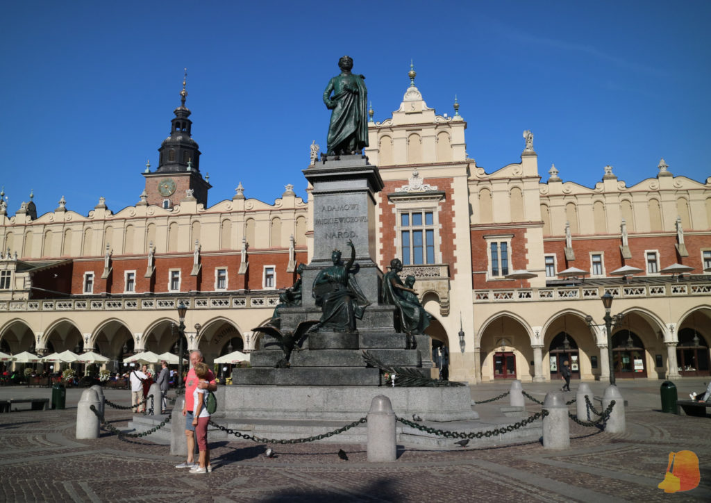 En el centro de la plaza se ve la Lonja de Paños, un edificio de dos plantas rojo y blanco, detrás se ve la torre del ayuntamiento.