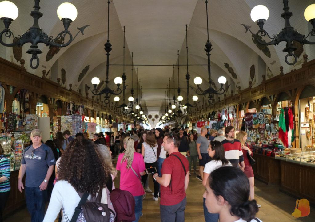 Imagen del interior de la Lonja de los Paños. Los puestos están a los lados y por todos lados se ve a mucha gente visitándolo.