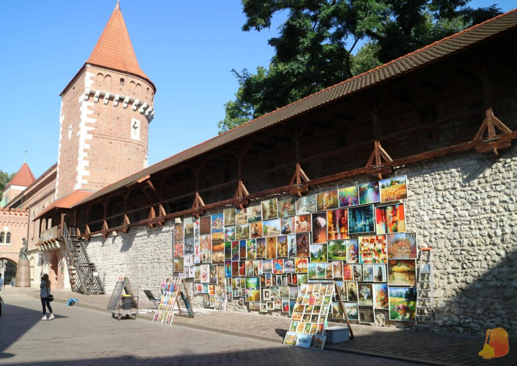 En el fragmento de la muralla que se conserva los artistas colocan cada día sus obras de arte. El contraste entre los muros de piedra y ladrillo y el color de los cuadros es precioso.