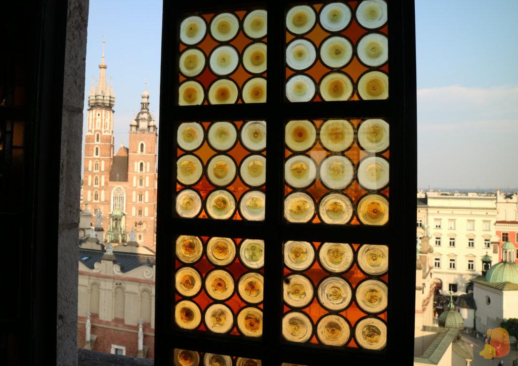 En la imagen se ve una ventana de la torre del ayuntamiento, con su cristalera de tonos naranjas, y por el hueco de la ventana se ve la Basílica