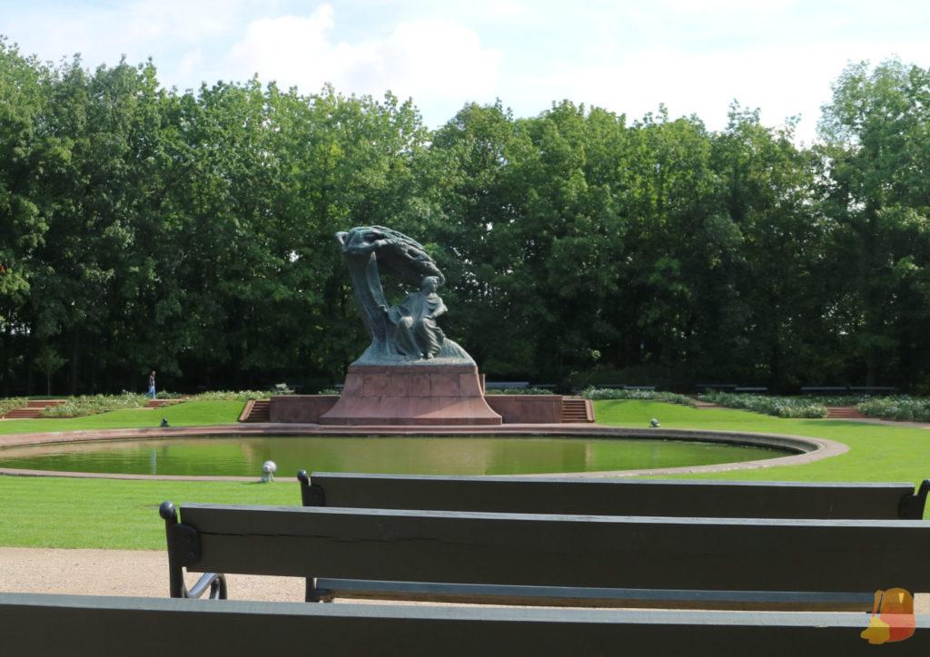 Junto a una laguna hay una estatua de Chopin sentado bajo un sauce