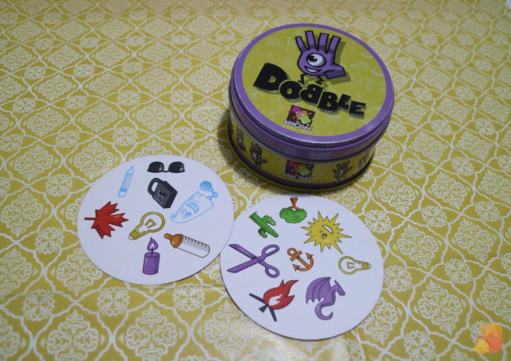 Se ve la lata del juego y dos cartas