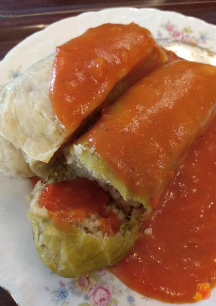 Rollitos de col rellenos de carne y arroz y servidos con salsa de tomate