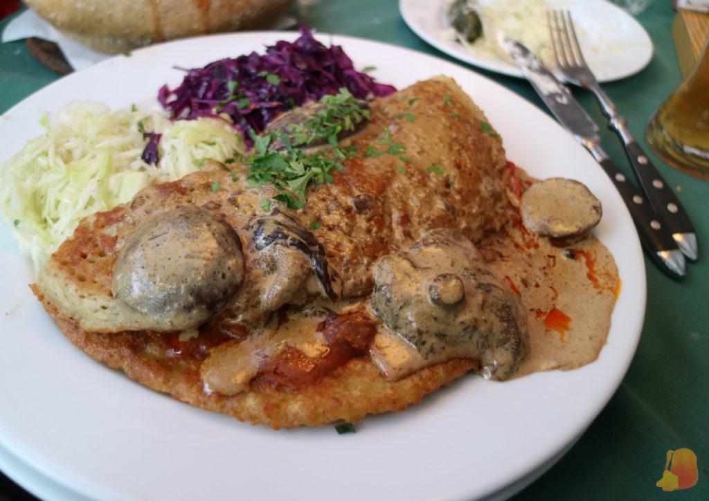 Tortita de patata servida con salsa de setas y con guarnición de col blanca y remolacha