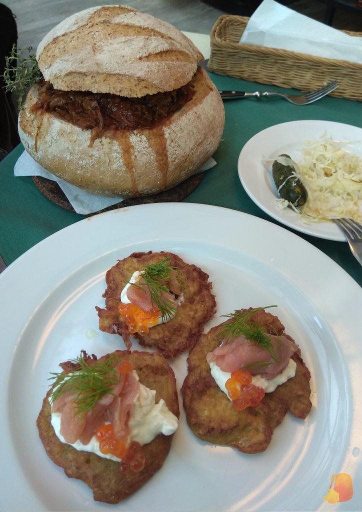 En primer plano tortitas de patata con salmón y detras bigos servido en un bollo de pan