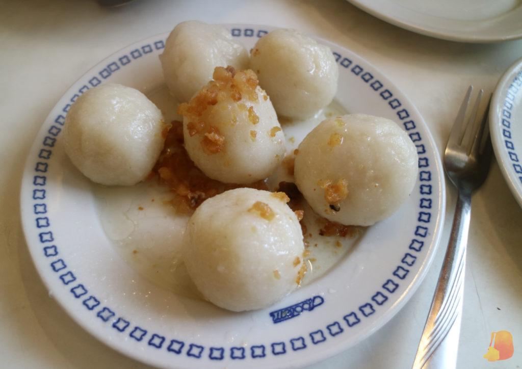 Bolas de patata servidas con virutas de cebolla por encima.