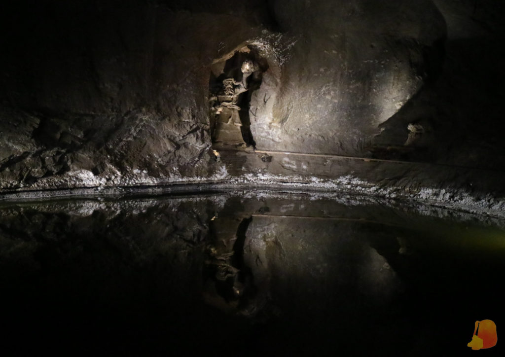 Lago de salmuera subterráneo. En un recoveco de la pared de la sala se ve una estatua de sal sosteniendo una antorcha