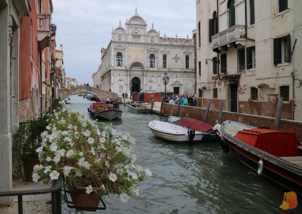 Un balcón con flores, un canal y una iglesia cualquiera forman una postal preciosa del barrio
