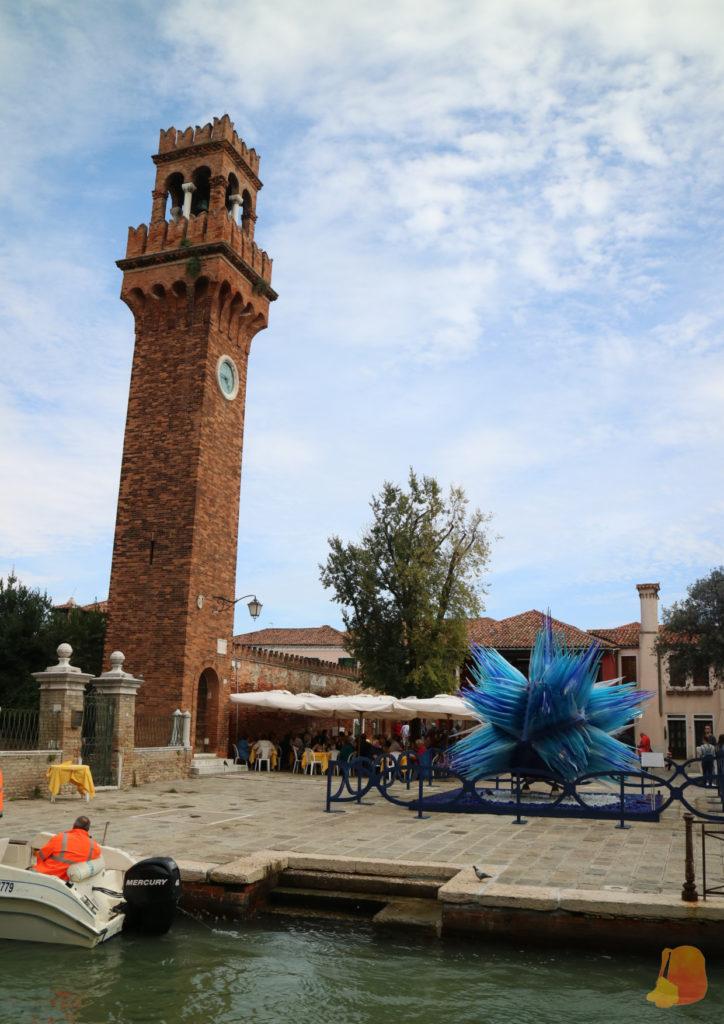La torre del reloj de Murano y frente a ella un monumento de un cristal de color azul