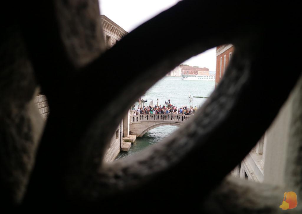 Fotografía sacada desde el interior del Puente de los Suspiros. Por uno de los huecos de la decoración se ve el exterior y el puente desde el que los turistas le sacan la foto por fuera
