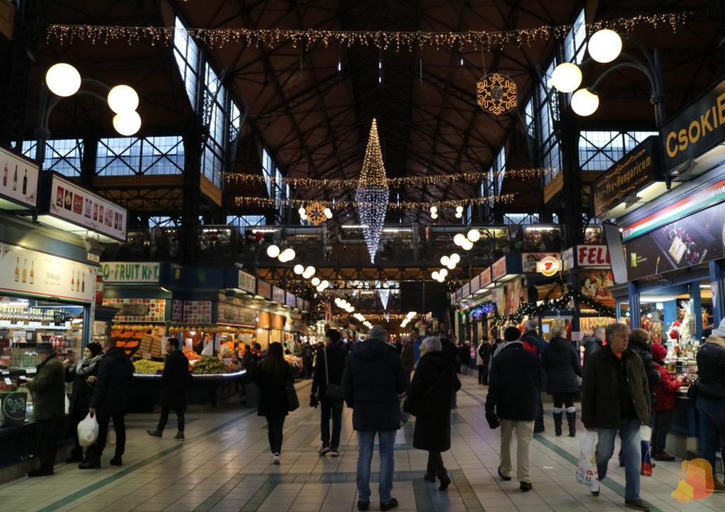 Planta baja del mercado con puestos de comida a los lados y las luces de Navidad colgadas del techo.