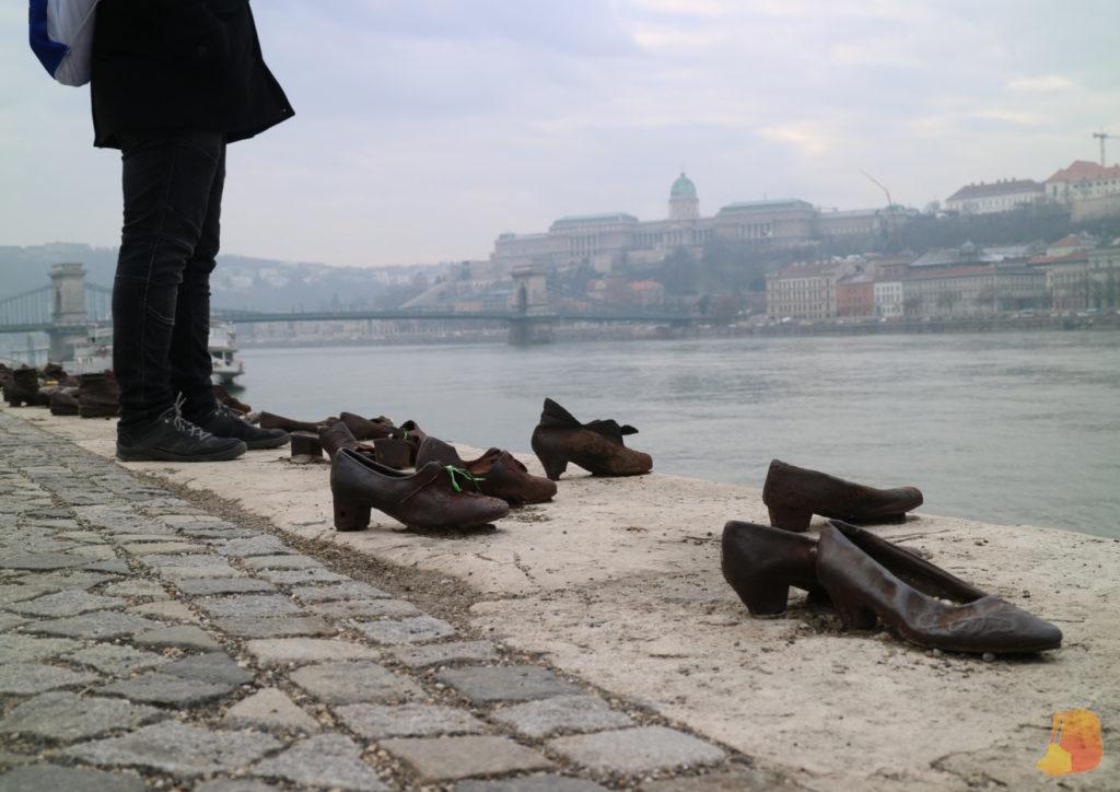 Pares de zapatos a la orilla del Danubio y de fondo el Puente de las Cadenas y el Castillo de Buda