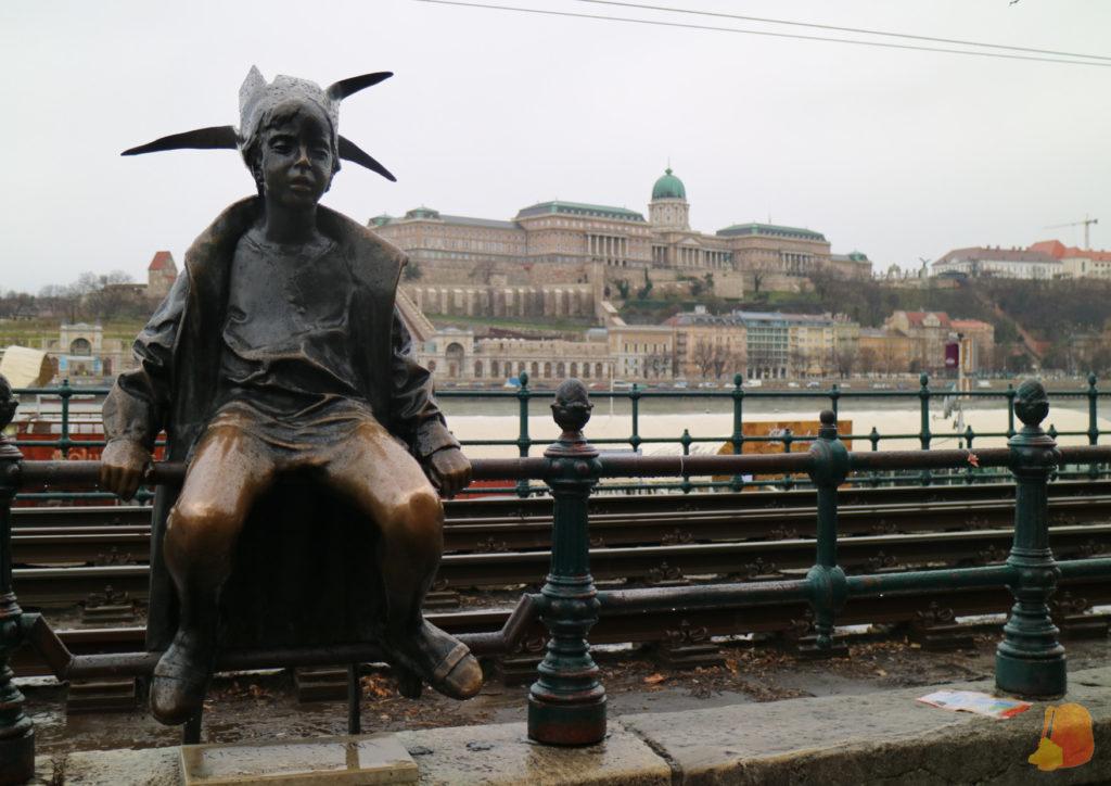 Estatua de una niña con una corona de cartón sentada sobre la barandilla. Al fondo se ve el Castillo de Buda
