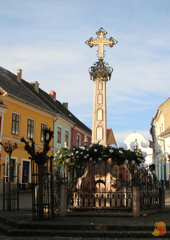 Cruz conmemorativa con adornos navideños. Detrás se ven las fachadas de colores que rodean la plaza