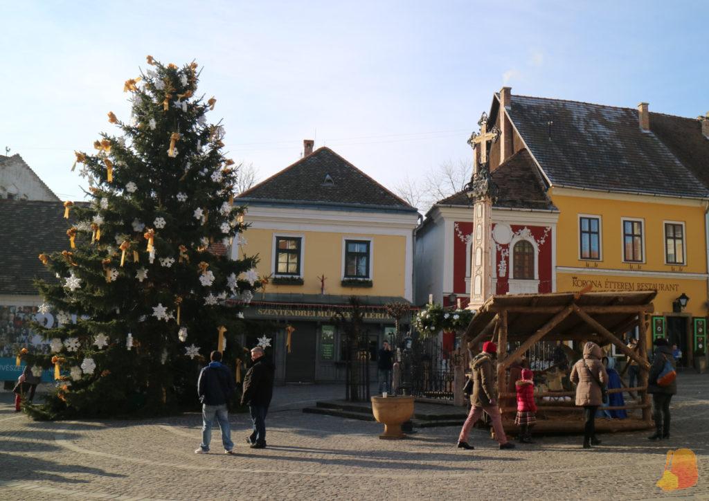 Plaza con el arbol de navidad, una cruz conmemorativa y un belen