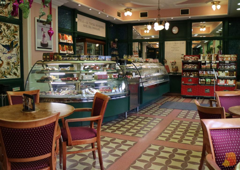 La cafetería tiene un estilo muy elegante. Se ve el mostrador y un par de mesas.