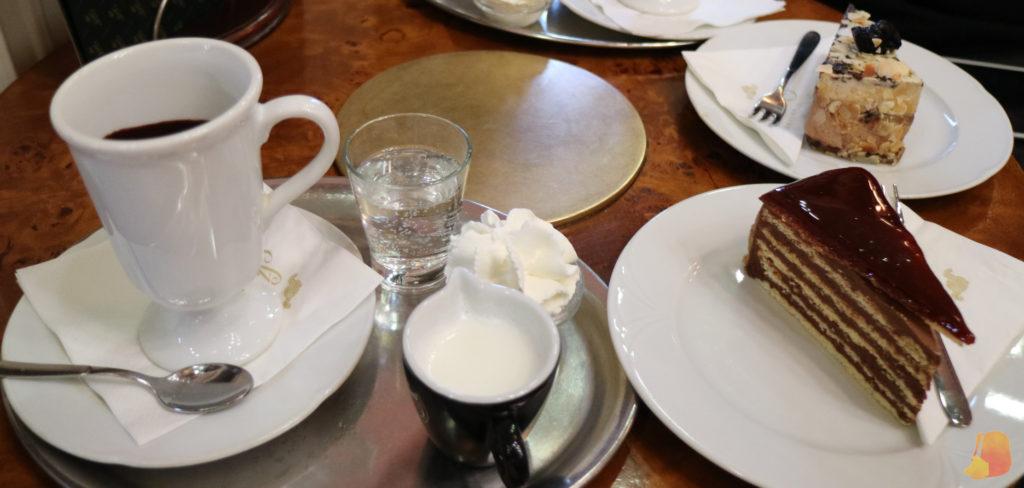 Taza de chocolate y dos pedazos de tarta. La que se ve más cerca es la Dobos Cake, de chocolate y galleta