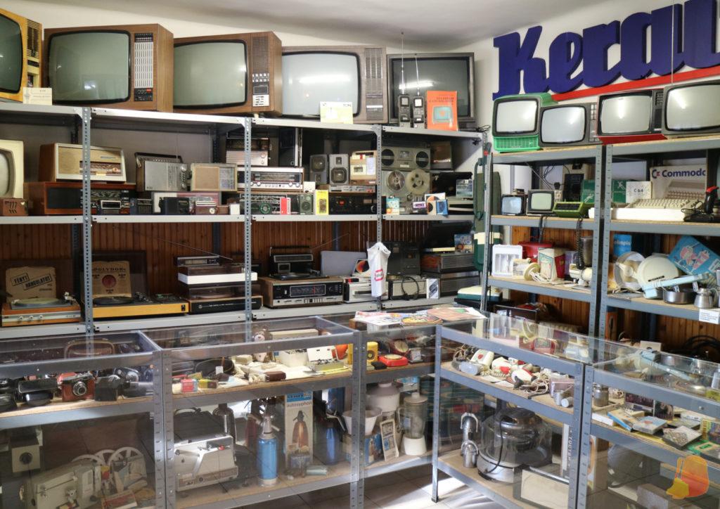 Sala repleta de objetos electrónicos de los 70: televisores, radios...