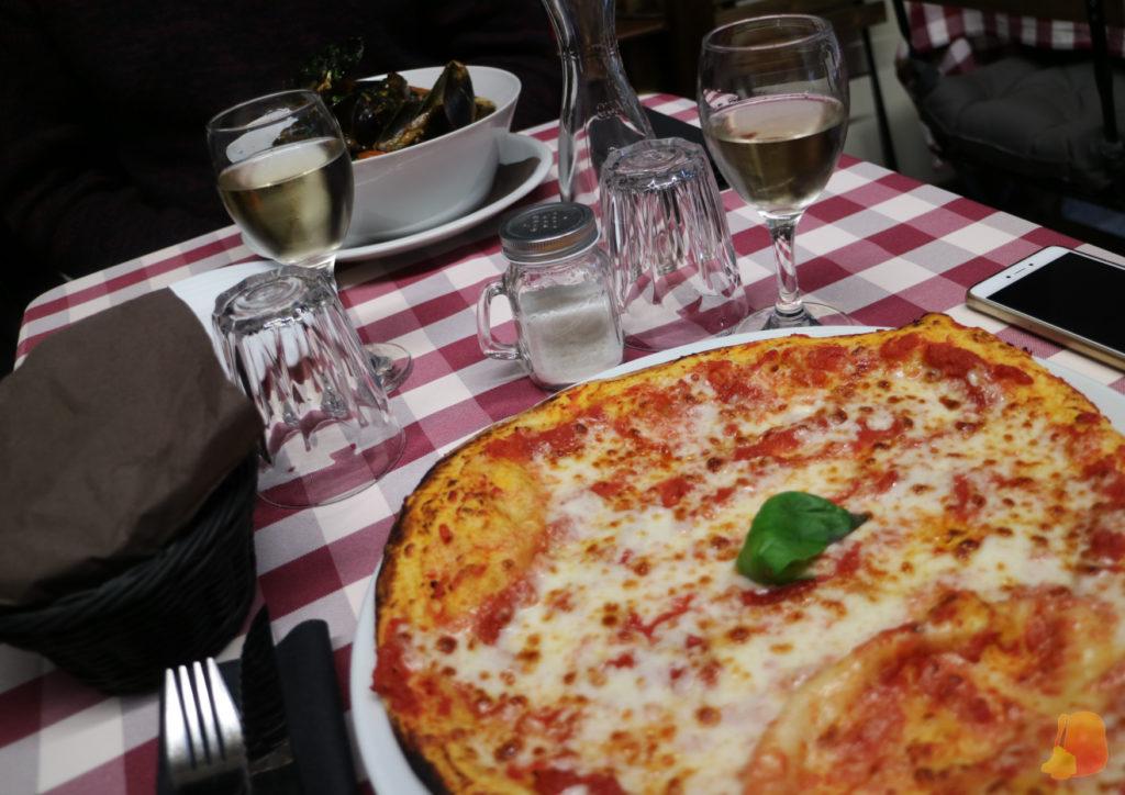 Pizza margarita para mí, dos copas de vino y un plato de espaguetis con mejillones para mi acompañante