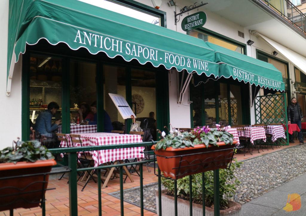 Fachada del restaurante con toldo verde y mesas con manteles a cuadros