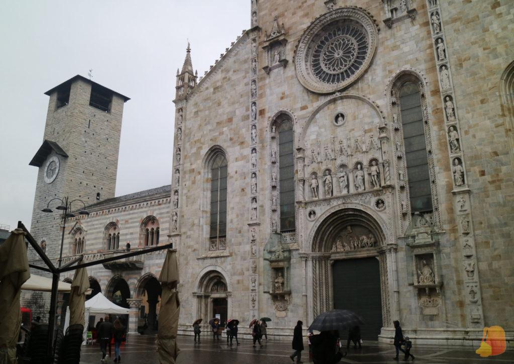 La fachada del Duomo es de mármol blanco y destacan las vidrieras y el rosetón. En el lado izquierdo se alza el Campanario.