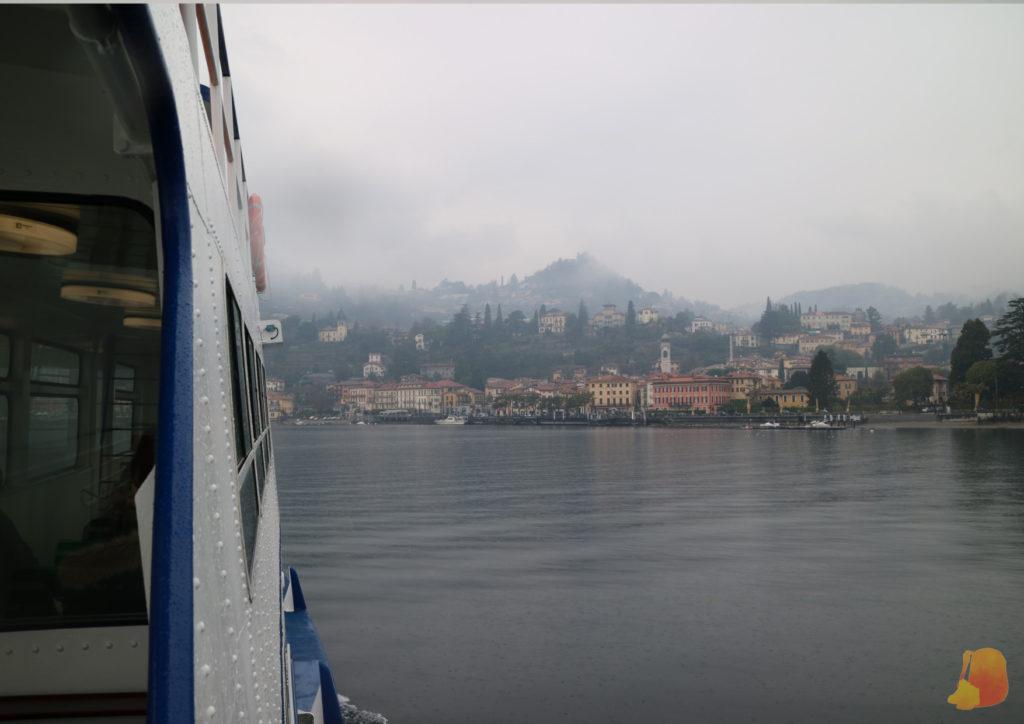 Se ve el lateral del barco y de fondo la ciudad de Mennagio. La ciudad está en el margen del lago, y se ve como se van escalonando las casas conforme se eleva la montaña.