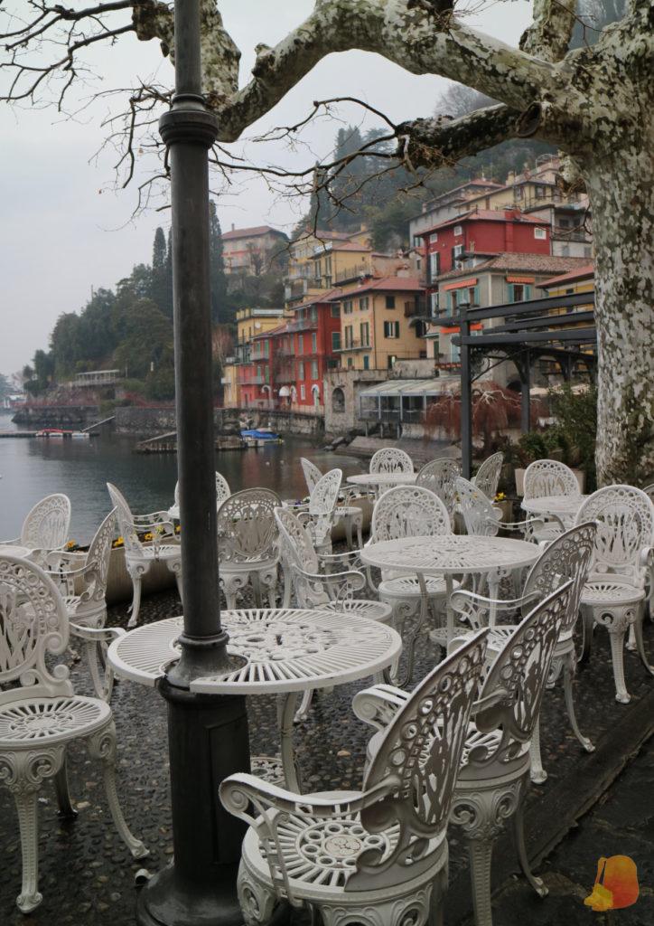 En primer plano se ven unas mesas y sillas blancas, de estilo clásico y de fondo se ve el perfil de la ciudad con sus casas de colores escalonadas entre el lago y la montaña.