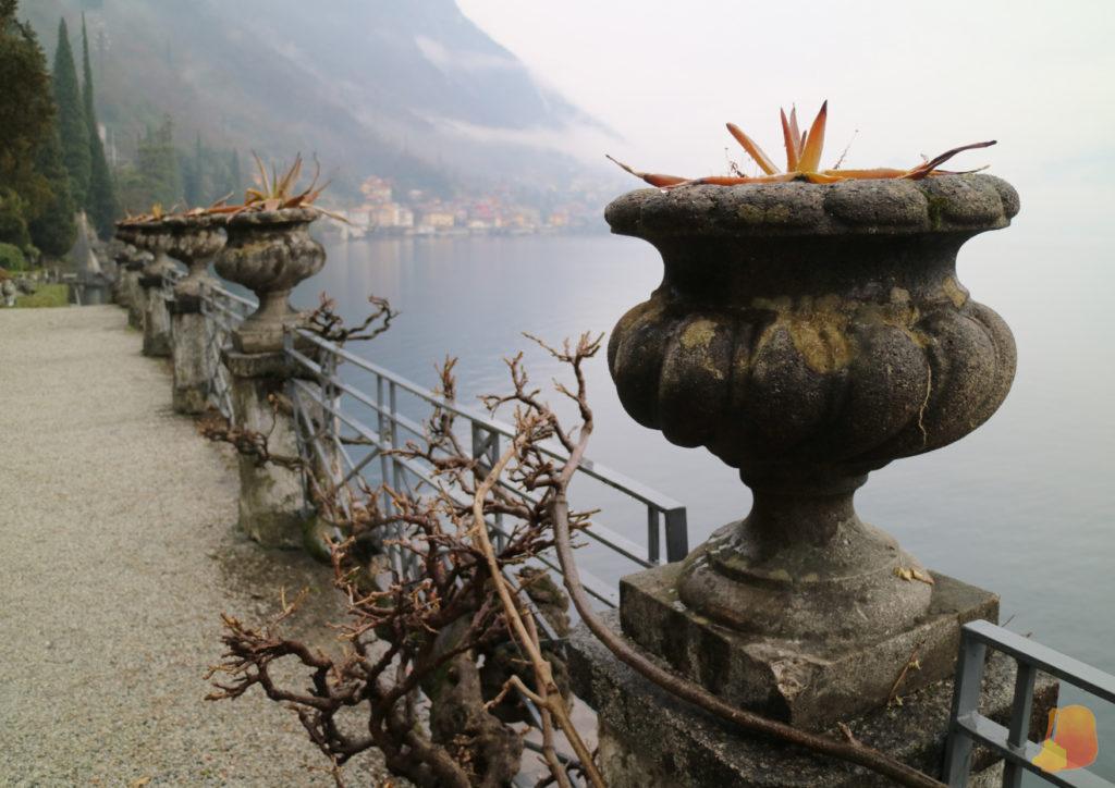 Baranda con maceteros de piedra de estilo neoclásico. Se ve las vistas del lago y se intuye otra ciudad al fondo.