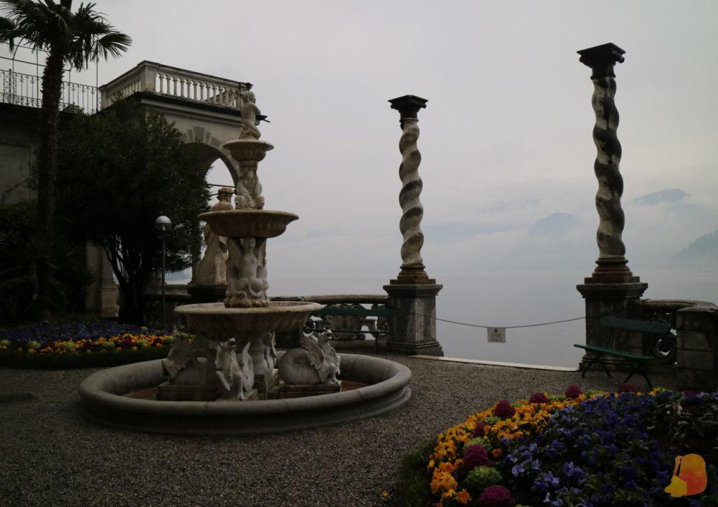 Terraza con una fuente y dos columnas salomónicas que flanquean un acceso al lago.