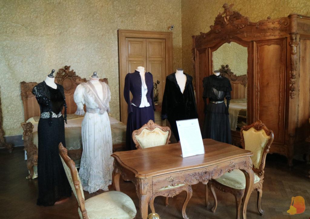Dormitorio con cama, armario, mesa y tres sillas de madera. En el centro de la sala hay cinco maniquíes con vestidos de época