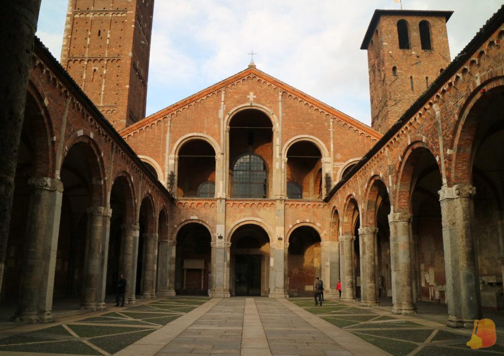 Patio de entrada a la Basilica, con arcadas a los lados. La iglesia es de ladrillo rojo. A cada lado se levantan dos torres asimétricas. La de la derecha es más baja que la otra.