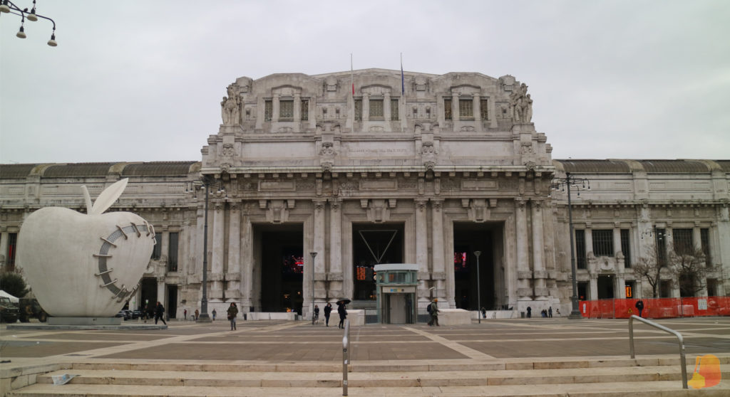 Fachada de la Estación de trenes con tres puertas monumentales. En la plaza que hay frente a la estación hay una estatua de una manzana gigante.
