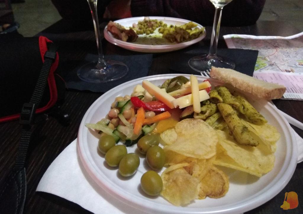 En mi plato hay patatas fritas, olivas, quesos, macarrones y ensalada de garbanzos. De beber hay dos copas de vino blanco