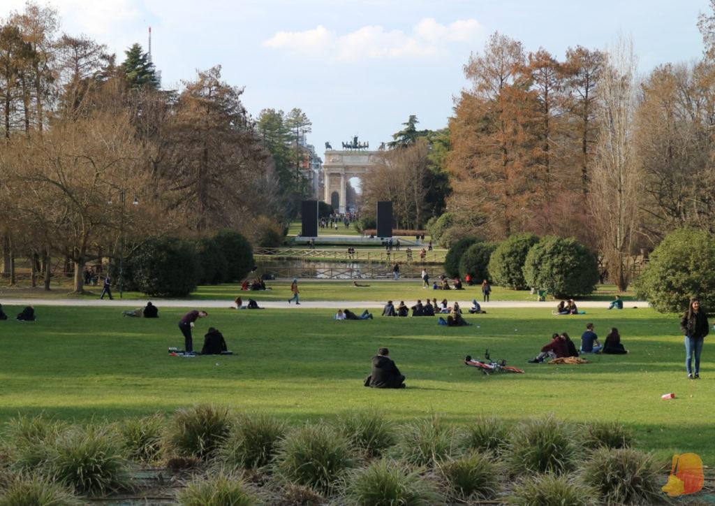 Gran explanada de césped donde hay mucha gente sentada. Se ve al fondo un lago artificial y más allá un Arco triunfal.