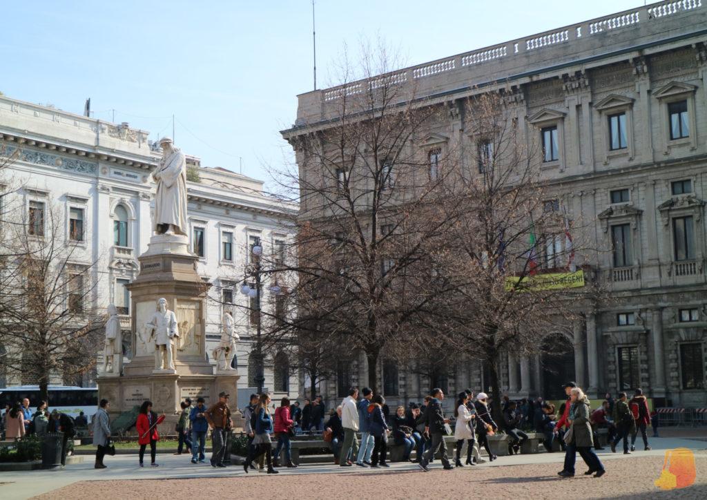 Plaza llena de gente con una escultura en el centro de un señor con túnica.