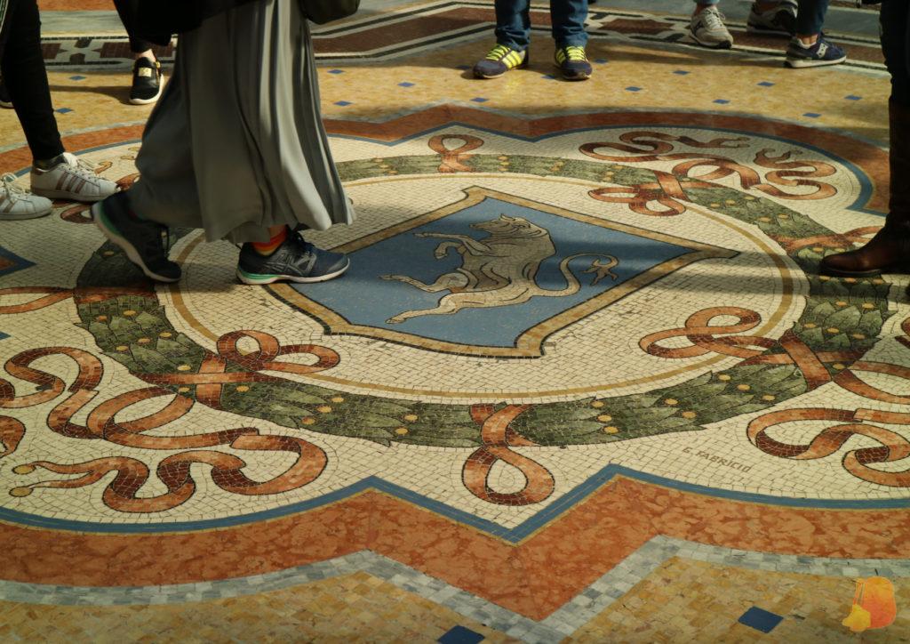 Mosaico en el suelo con un escudo azul con un toro en el centro.