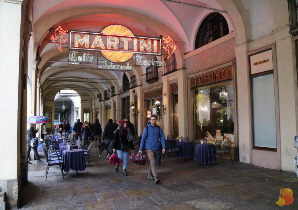 Entrada del Café Torino. La terraza está dentro de las arcadas que rodean la plaza y sobre ella está un neón que pone Martini