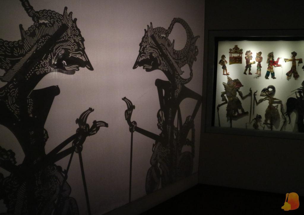 Vitrina con marionetas para el teatro de sombras de Indonesia. Junto a ella se ven las sombras.